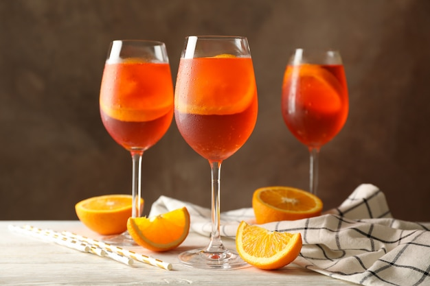 Composition with aperol spritz cocktail against brown.