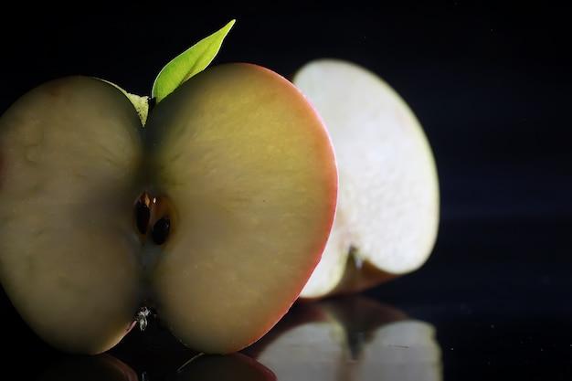 黒の背景にリンゴのスライスとの構成。水滴と黒の背景にバックライトとリンゴのスライス。テーブルの上のジューシーなリンゴ。