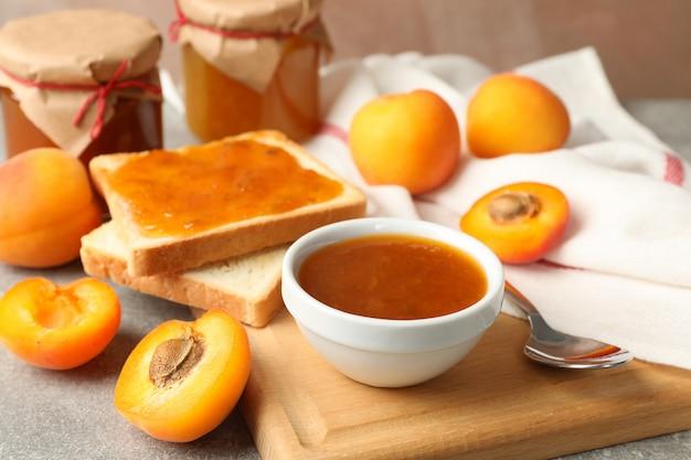 Композиция с абрикосовым джемом на сером столе, крупным планом