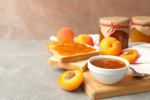 Композиция с абрикосовым джемом на сером столе, место для текста
