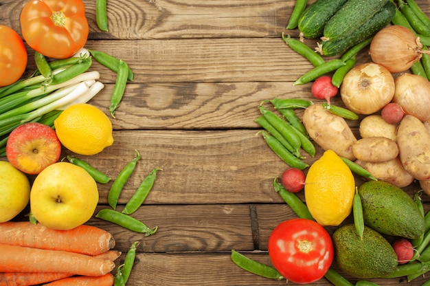 Композиция с ассорти из свежих органических овощей и фруктов. огурцы, помидоры, редис, авокадо, горох, картофель, лимон, лук. еда на темной деревянной поверхности.