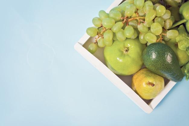 生の有機野菜の盛り合わせと白い木製トレイに果物のコンポジション。上面図。コピースペース。