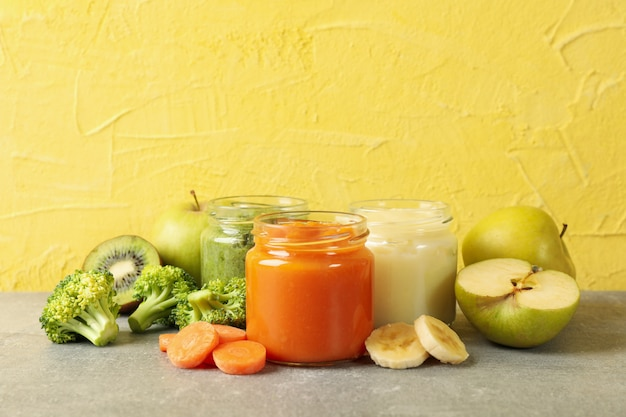 Composition with baby food on gray table against yellow background