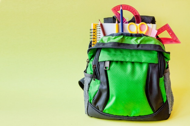 Composition with backpack and school stationery on yellow