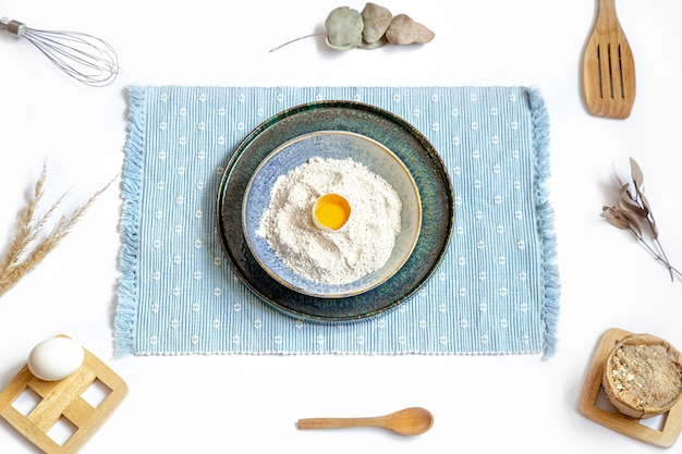 Композиция с ингредиентами для выпечки и кухонными принадлежностями на белом столе.