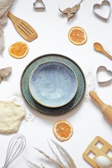 Composizione con ingredienti da forno e accessori da cucina su un tavolo bianco vista dall'alto.