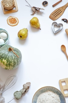Composition with baking ingredients and kitchen accessories on a white table top view.