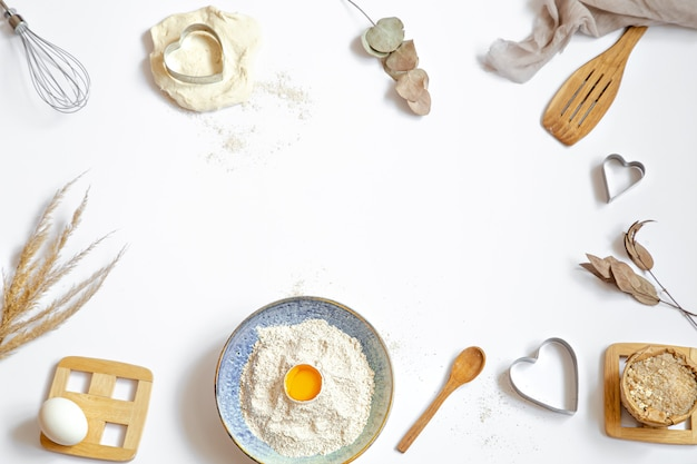 Composition with baking ingredients and kitchen accessories on a white table.