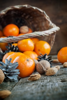 Composition with basket,tangerines and nuts wooden background