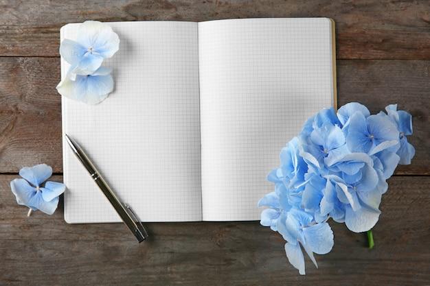 美しい青い花、ノートブック、木製の背景にペンで構成