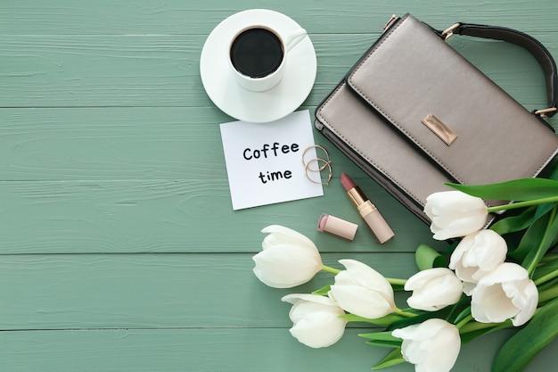 美しいチューリップ、女性のアクセサリー、カラーの木製テーブルにコーヒーを入れたコンポジション '