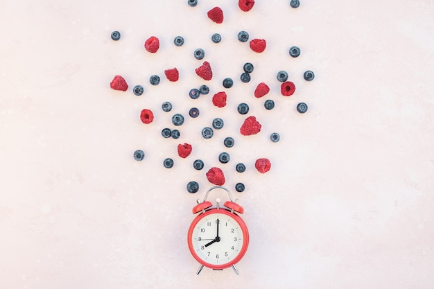 Composition with berries and red alarm clock