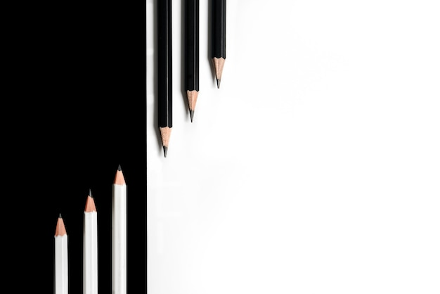 Composition with black pencils on a white surface and white pencils