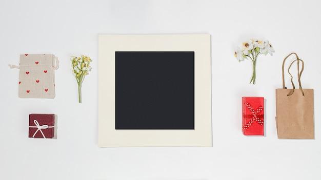 黒のフォトフレーム、赤いギフトボックス、クラフトバッグ、赤いハートの形のキャンバスバッグ、白い背景の上の春の野の花のコンポジション。トレンディなフラットレイモックアップ