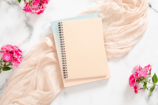 Composition with blank paper notebook, pink flowers and pastel blanket