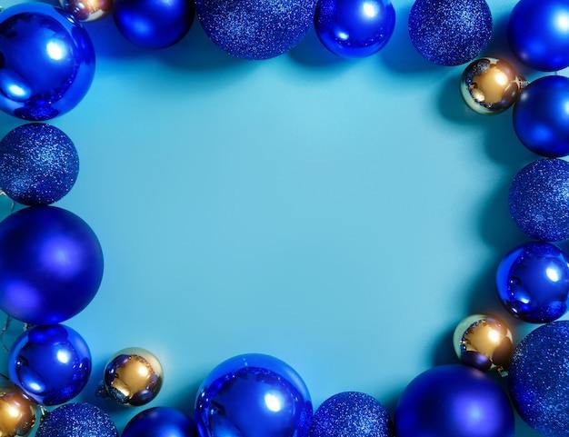 コピースペースのある青い背景に青と金のクリスマスボールで構成。クリスマスフレーム。