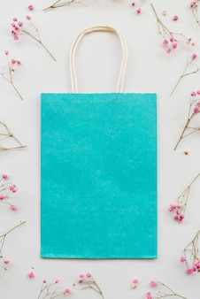 Composition with blue package and pink flowers