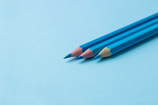 Composition with blue pencils on a bright blue background. close-up. place for text.