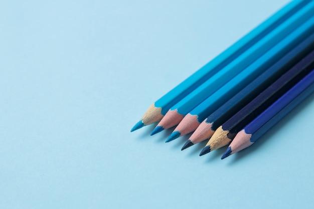 Композиция с синими карандашами на ярко-синем фоне. крупный план. место для текста.