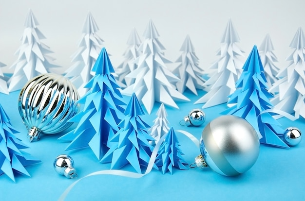 Composition with blue and white paper christmas trees and ball decorations