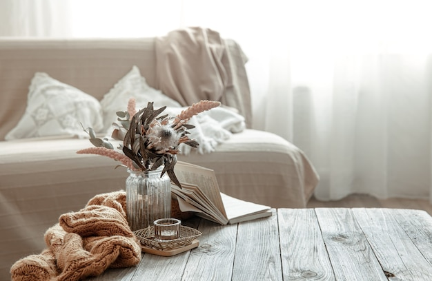 Composition with a book, a dry flower and a knitted element in the interior of the room.