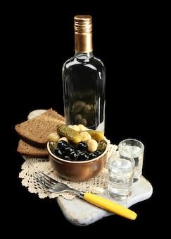 Композиция с бутылкой водки и маринованными овощами, свежим хлебом на деревянной доске на черном