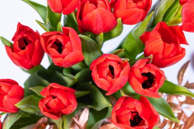 Композиция с букетом тюльпанов на белой поверхности, вид сверху