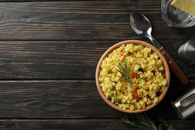 Композиция с миской вкусного риса на деревянной поверхности