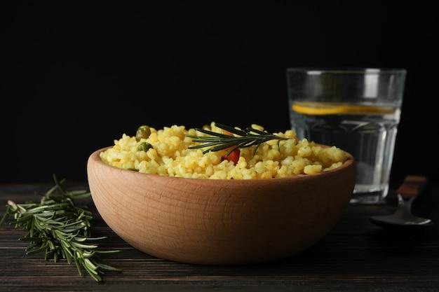 Композиция с чашей вкусного риса на деревянном столе, крупным планом