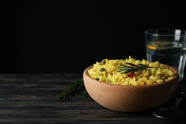 Композиция с чашей вкусного риса на деревянном столе, копией пространства
