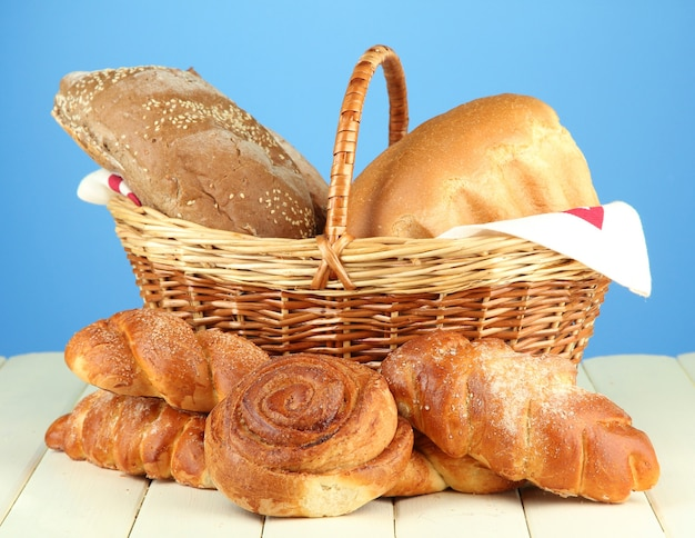 블루에 나무 테이블에 고리 버들 세공 바구니에 빵과 롤, 구성