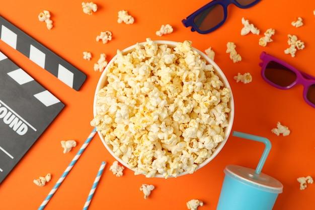 Композиция с ведром попкорна на оранжевом пространстве. пища для просмотра кино