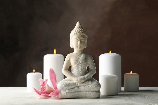 仏と木製のテーブルの上のろうそくの組成物。禅のコンセプト