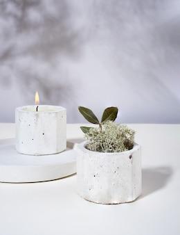 콘크리트 촛대에 콩 왁스 향초를 태우는 구성. 말린 꽃, 이끼. 벽에 그림자. 미니멀리즘.