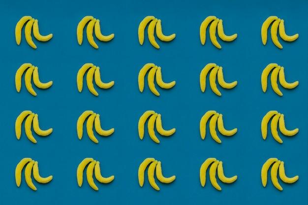 Композиция с конфетами бананов и синим фоном