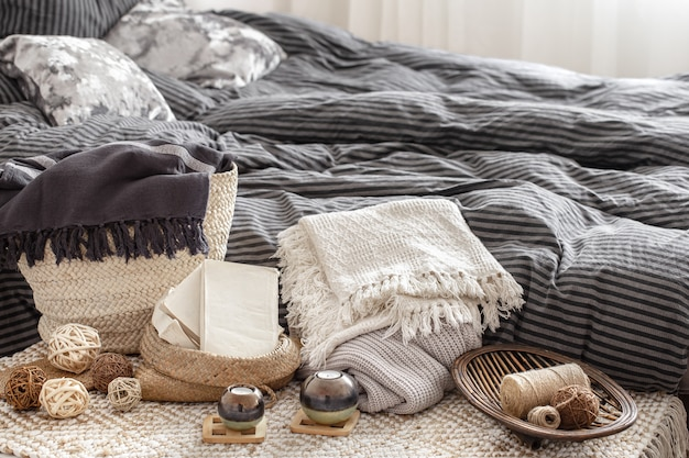 Composition with candles, knitted elements and other decor details in the bedroom.