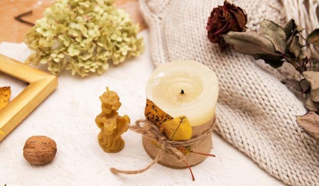 Композиция со свечами с опавшими листьями, сухой розой, свитером. осенняя концепция