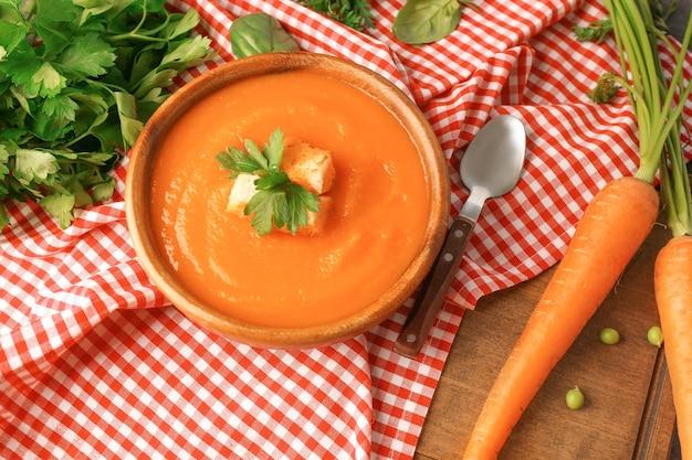 Композиция с морковным крем-супом на деревянном столе