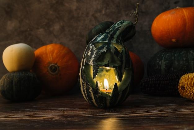 Композиция с вырезанной зеленой тыквой и освещенной свечой