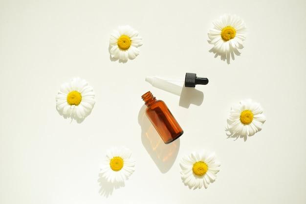 Композиция с цветами ромашки и косметической бутылкой эфирного масла
