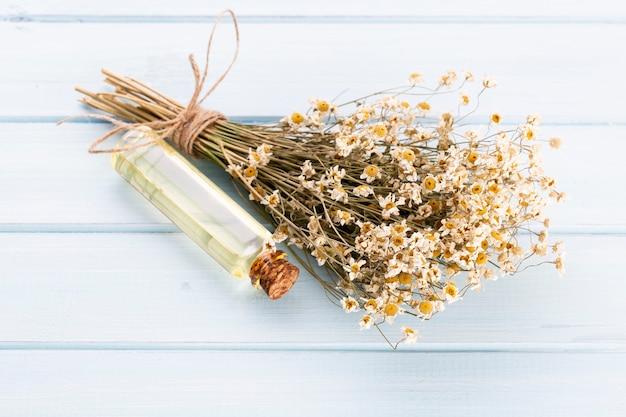 カモミールの花と自家製化粧品、エッセンシャルオイル、ソーパ、白い背景、上面図で構成。