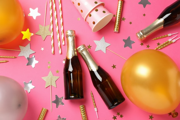 Composition with champagne and birthday accessories on pink background, top view