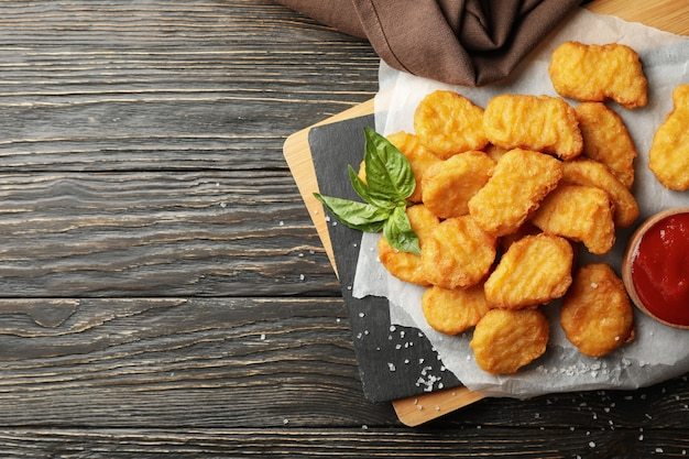 Composition with chicken nuggets and ketchup on wooden background