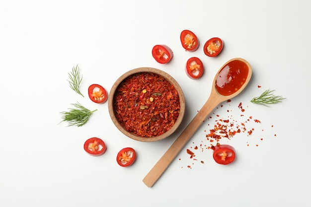Composition with chilli pepper, spice and sauce on white wall