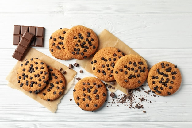 Composition with chip cookies and chocolate on white wooden background