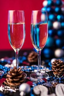 Композиция с рождественскими и новогодними украшениями 2020 и двумя бокалами для шампанского на ярком фоне
