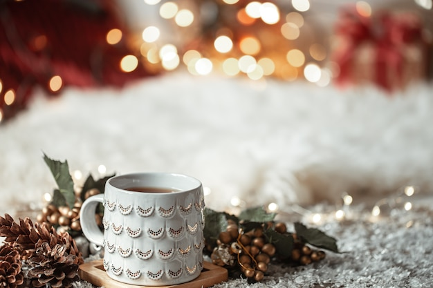 Composition with christmas cup with hot drink on blurred abstract background