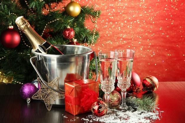 明るい背景に、クリスマスの装飾と2つのシャンパングラスで構成