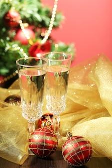 밝은 배경에 크리스마스 장식과 샴페인 잔 2개가 있는 구성