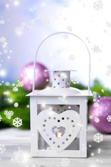 밝은 배경에 크리스마스 랜턴, 전나무 및 장식으로 구성